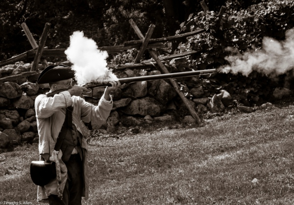 Ed Wilder, a National Park employee in 1775 period clothing firing a musket outside the Hartwell Tavern, Lincoln, MA. August 29, 2015