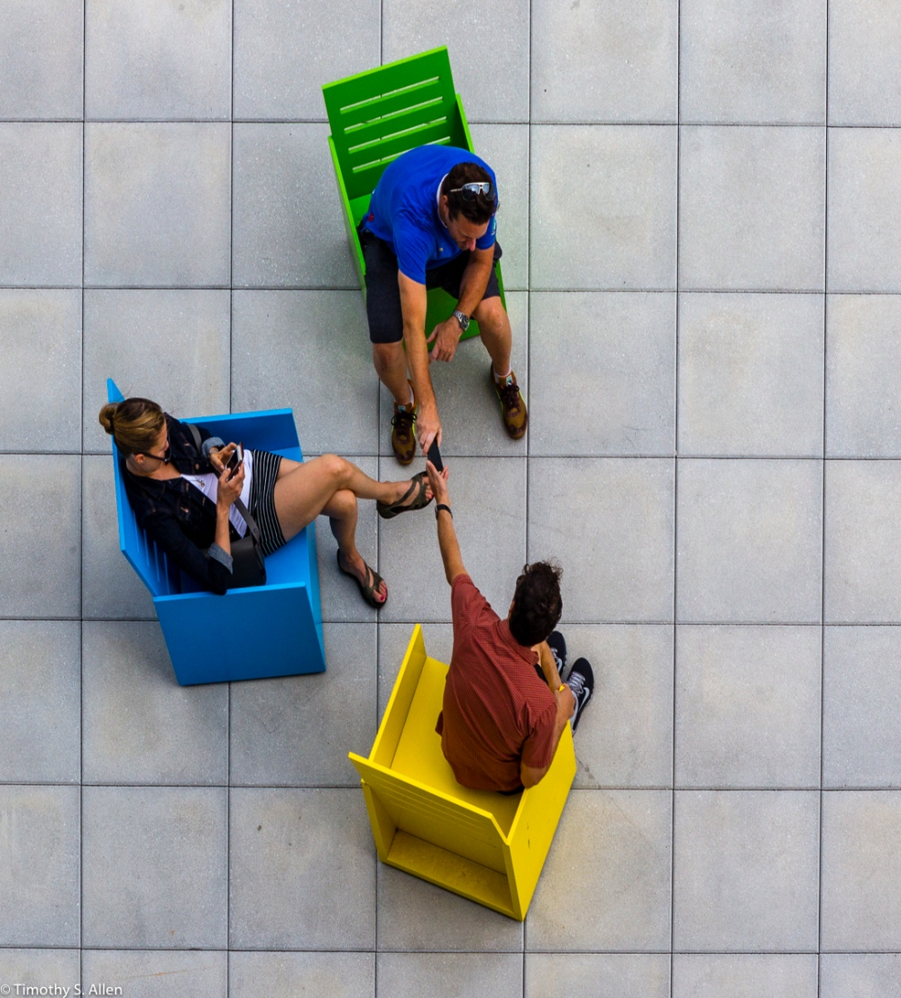 """Three Sitting in Mary Heilmann's """"Sunset"""" chairs on the 5th floor outdoor gallery, of the Whitney Museum of American Art, 99 Gansevoort St, New York City, NY, USA September 4, 2015"""