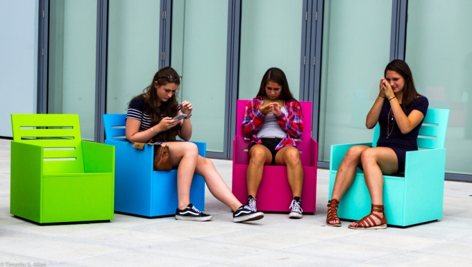 "Three Sitting in Mary Heilmann's ""Sunset"" chairs on the 5th floor outdoor gallery, of the Whitney Museum of American Art, 99 Gansevoort St, New York City, NY, USA September 4, 2015"