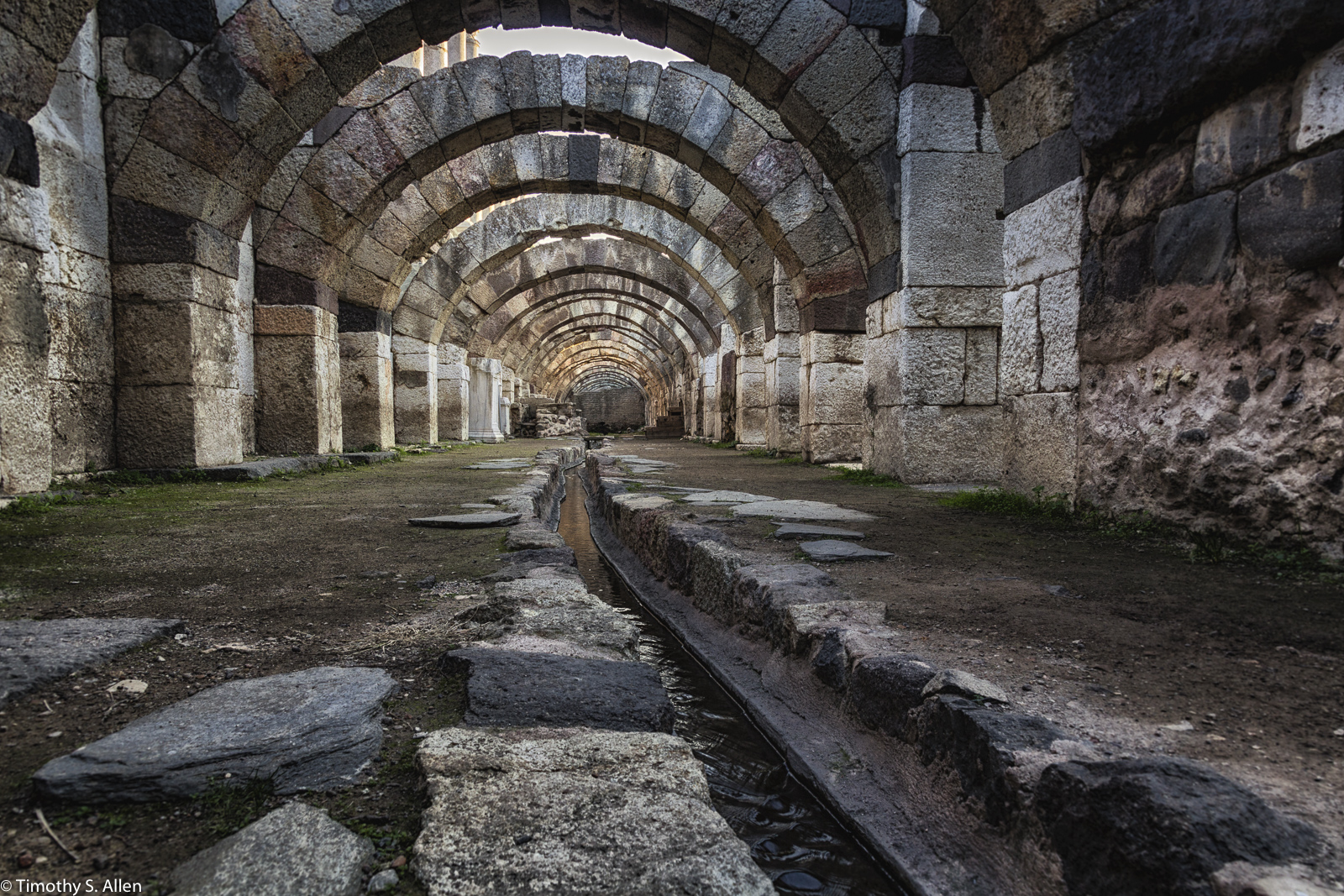 Street in Agora, Ancient Historic Site, Izmir, Turkey December 13, 2015 Agora, ancient market place, was first built in the 4th century BC to the north of Pagos (Kadifekale) where Smyrna was moved after Bayrakli. Like all other Agoras of the ancient world, it was a meeting place for all commercial, political, and religious activities for the local people. It was surrounded mostly by state buildings on a rectangular plan with a large central courtyard and a covered stoa around it. The agora was destroyed several times by strong earthquakes and it was rebuilt after each one of them, final restoration was done by Roman emperor Marcus Aurelius when a major earthquake hit the city in 178 AD. Northern and western stoas have been excavated including their basements, and a large 165 x 28 m basilica has been found on the northern stoa. One of the main streets of Smyrna city was cutting through the agora dividing it in two equal parts, and there were entrance gates at both ends. The excavation works are still ongoing at the agora for the basilica and a part of the eastern stoa. http://www.allaboutturkey.com/izm_site.htm