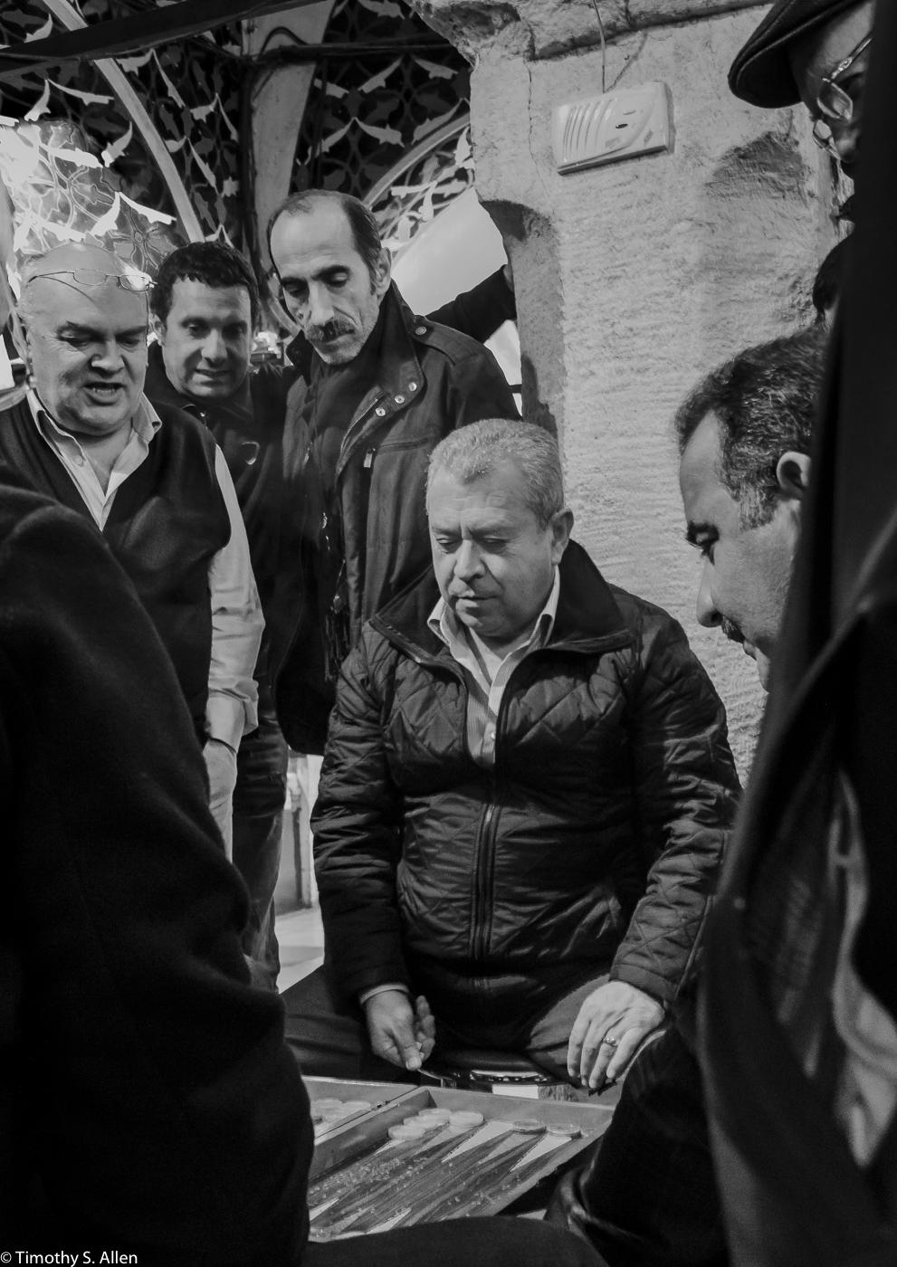 Intense Backgammon Game in the Istanbul Bazaar. Lots of Kibitzing Going On. Istanbul, Turkey - December 15, 2015
