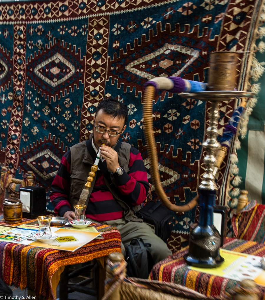 A Tourist Trying a Water Pipe in a Outdoor Restaurant Istanbul, Turkey November 24, 2015