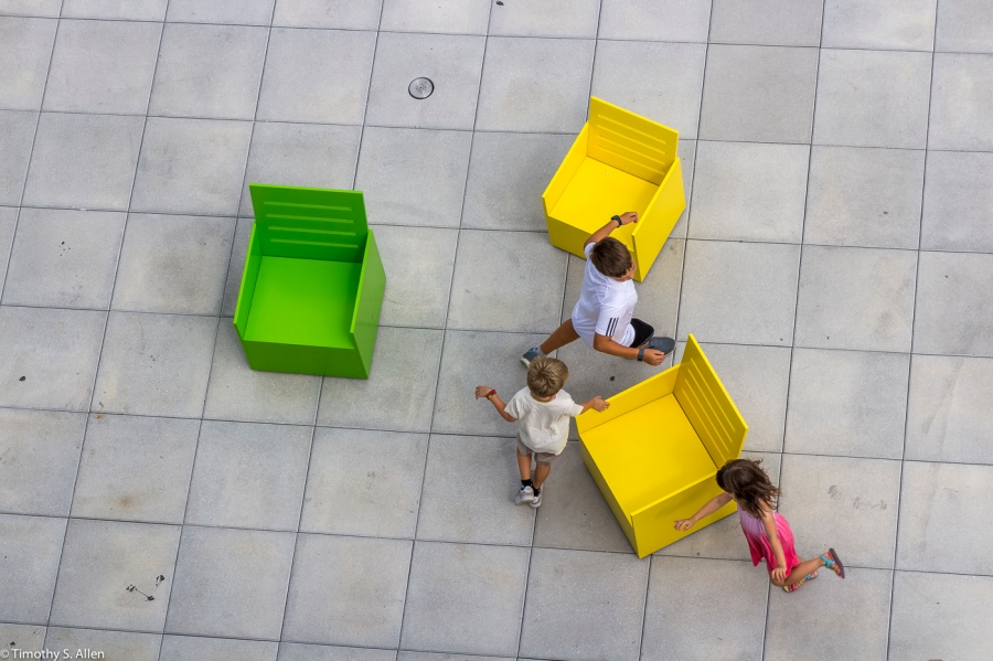 """Three Children Playing Musical Chair Amongst Three of Forty Chair in the Exhibition by Mary Heilmann's """"Sunset."""" Formerly located on the 5th floor outdoor gallery, of the Whitney Museum of American Art, 99 Gansevoort St, New York City, NY, USA September 4, 2015"""