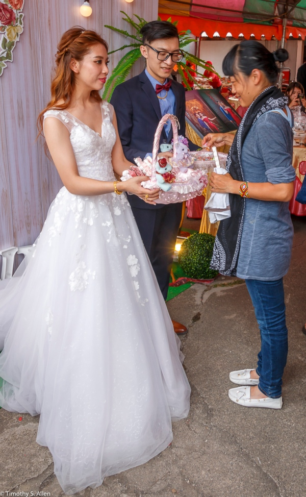 The Bride and Groom Saying Goodbye to Those Who Attended the Wedding Banquet. She is Offering Candies for Good Wishes. Chenglong Village, Kohou Township, Yunlin County, Taiwan April 28, 2018