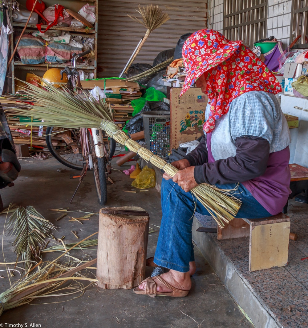 Ms Hsu is making traditional brooms In a small traditional village in Chaiyi County, Taiwan The brooms are made from palm leaves, a bamboo stick and sugar cane leaves. She told us that when she got married at 19 and moved to this village De Shin Li she had to learn how to make these traditional brooms as did all women living in this village. We had to buy two brooms, one to sweep the ground and the other to clean the ceiling. De Shin Li Village, Puzui Township, Chaiyi County, Taiwan May 10, 2018