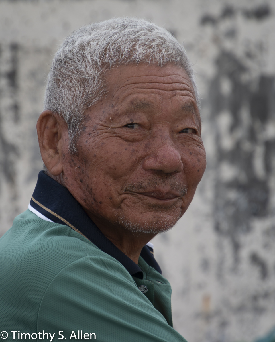 An elderly man paused to allow me to take a picture of him. A friend had stopped him to talk. Cheng long Village, Kohou Township, Yunlin County, Taiwan May 3, 2018