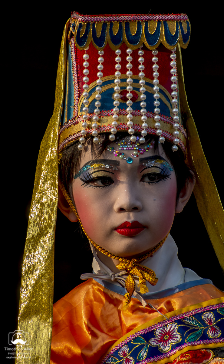 A young girl is dressed and made up to depict a character in a traditional Chinese story/myth. She rides on a float in the Mazu Parade. Beigong, Yunlin County, Taiwan, May 4, 2018.