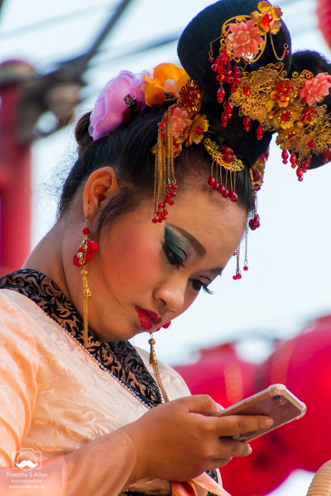 A model appear as a traditional Chinese woman for the Mazu festival. She continues to use 21st century technology while waiting for the Mazu parade she is riding on to begin. Beigang, Yunlin County, Taiwan, May 4, 2018.