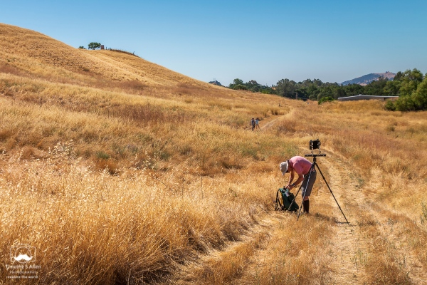 A photographer goes into his pack to get a film cartage to slip into the back of his 8x10 view finder camera. YoloArts - Arts to Farm event Pleasants Valley Farm, Vacaville, CA June 24, 2018.
