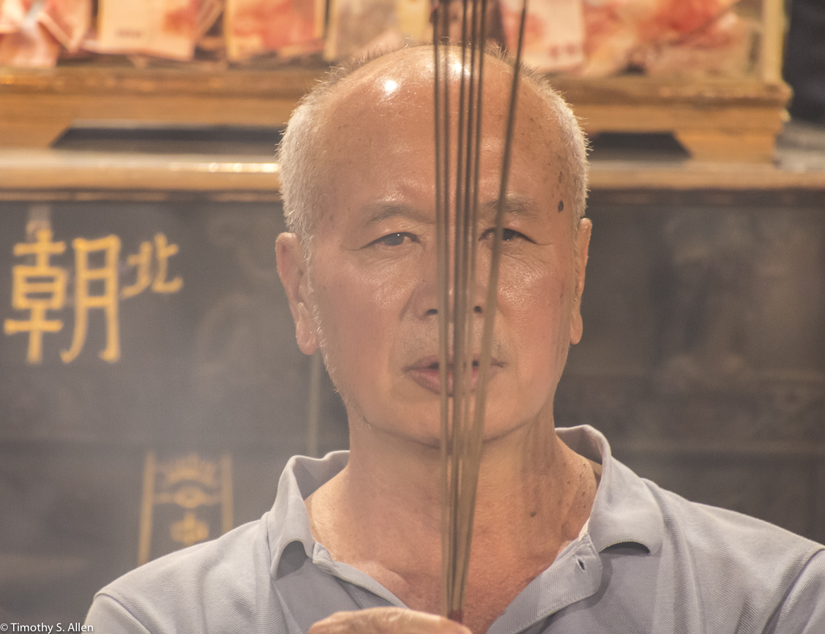 A man praying at the Beigang Chaotian Temple. He is holding incense sticks before a large smoky innocent burner/cauldron as he prays. He then place burning sticks in the cauldron. Beigang, Yunlin County, Taiwan May 4, 2018