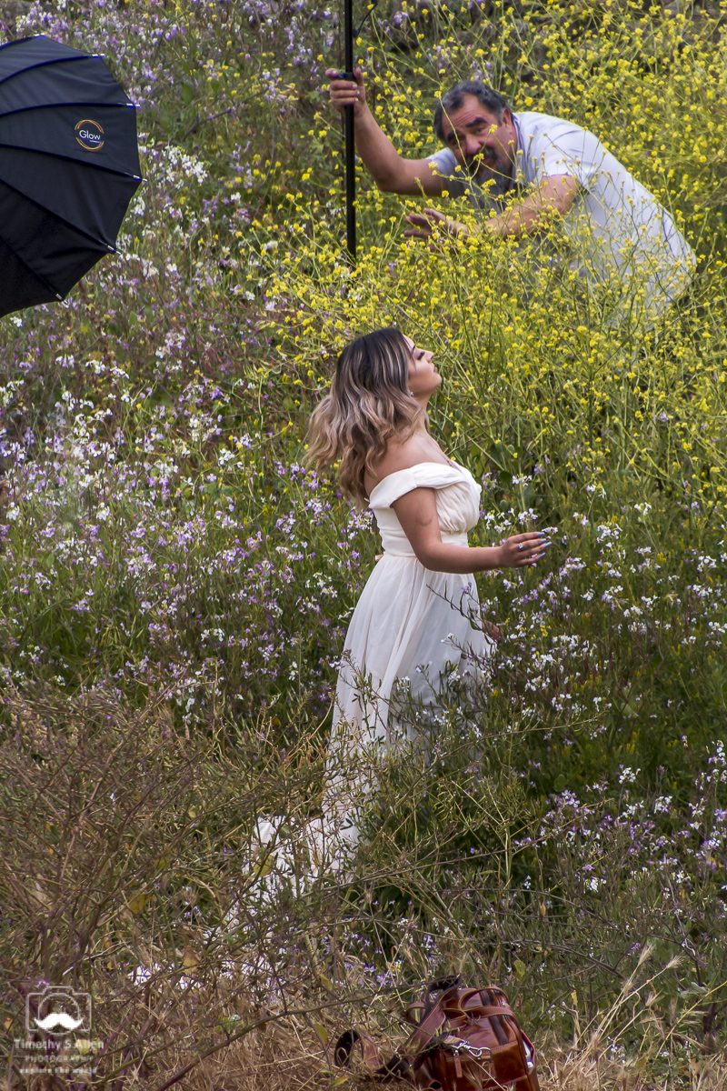 A photography class shooting models in a field on Cannery Row. The grip seems to be discouraging me from photographing her. Public spaces allow access to photography. No privacy here - at least in the United States. Monterey, California, June 19, 2018.