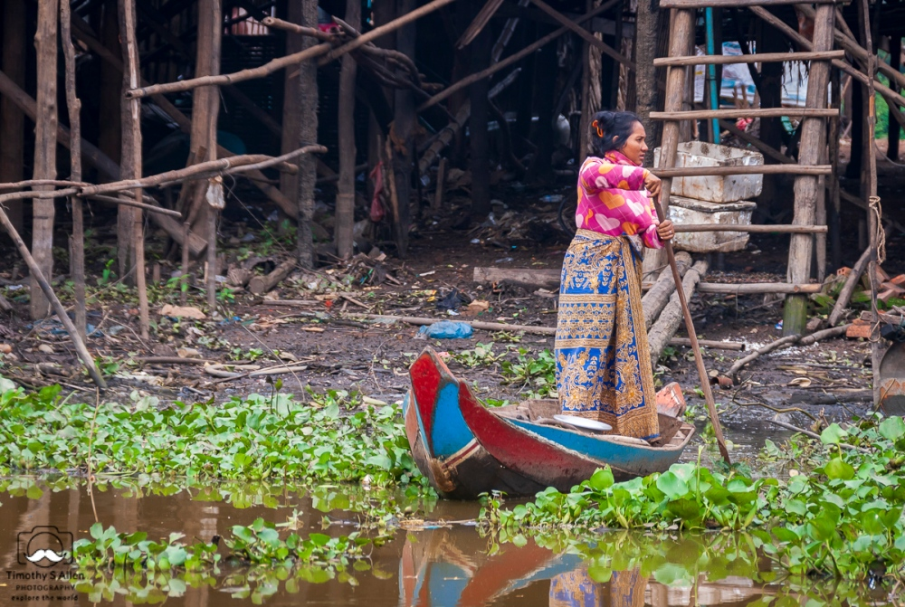Woman travels by boat. She lives in a village made of wood raised above the water on stilts. Tonke Sap Lake, Cambodia January 19, 2013