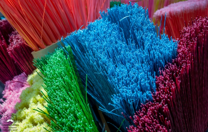 Colorful brooms are displayed with their bristles pointing up. Fulsom Street Flea Market, Sacramento, CA, U.S.A. 08-13-2013.