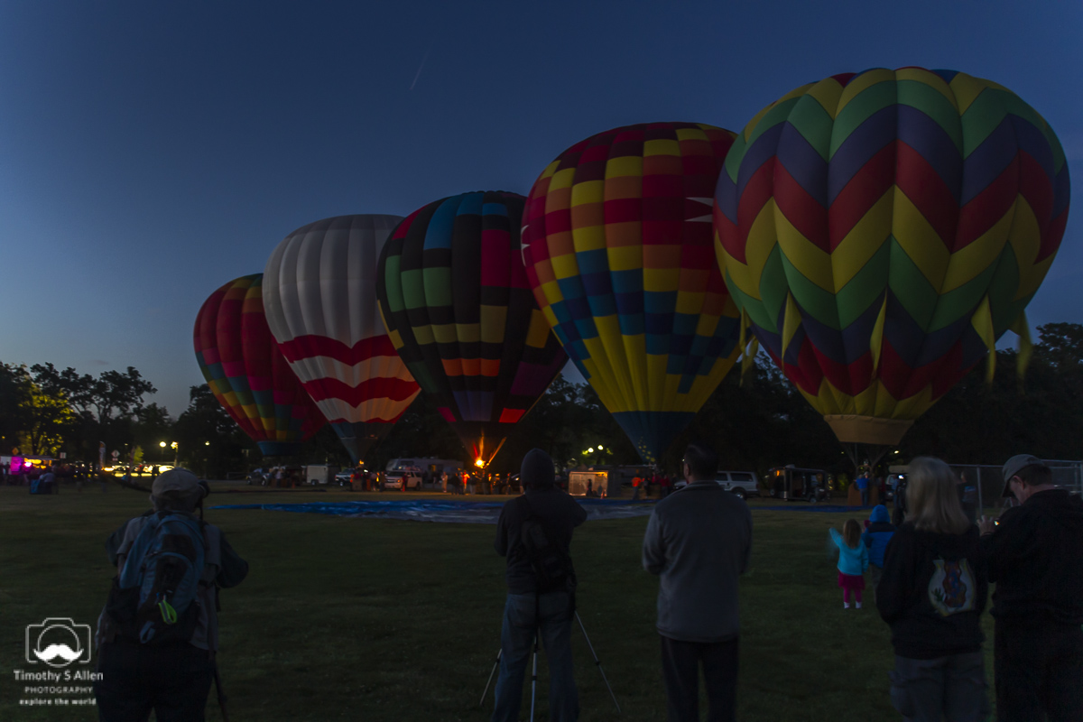 Four hot air balloons are dark having already heated the air enough to remain inflated. One balloon is preparing to turn up the gas. All at the Sonoma County Hot Air Balloon Classic. Windsor, CA, U.S.A. June 14, 2014.