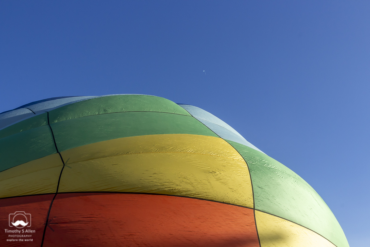 One kid sized helium balloons has escaped and rises high above while the hot air balloon remains on the ground as it is inflate with hot air. Windsor, CA, U.S.A. June 14, 2014